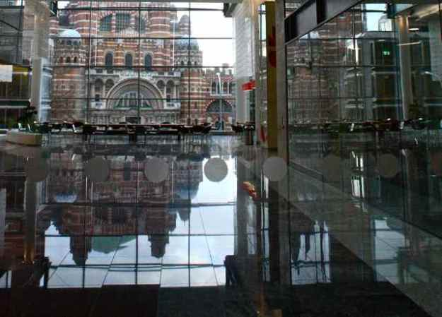 Brompton Oratory through a window and reflected in the Microsoft building.